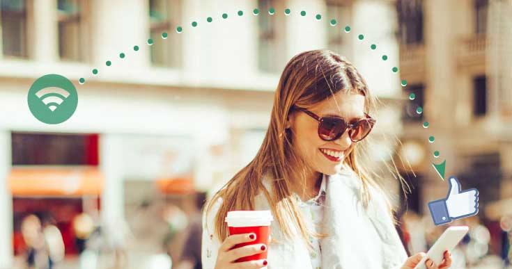 Junge Frau mit Einkaufstaschen, Kaffee und Smartphone