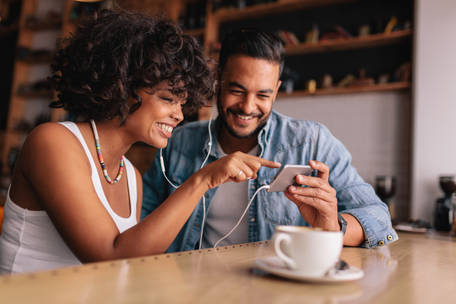 Smiling young couple with earphones sitting at coffee shop looking at mobile phone. Young man and woman at cafe using smart phone.